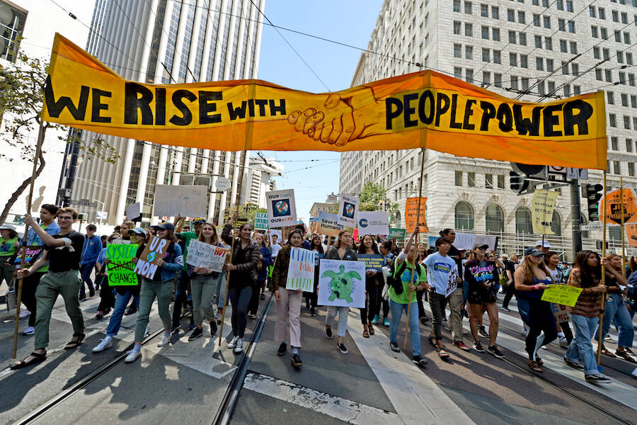 "Marchers carry a banner displaying the words ""We Rise With People Power"""