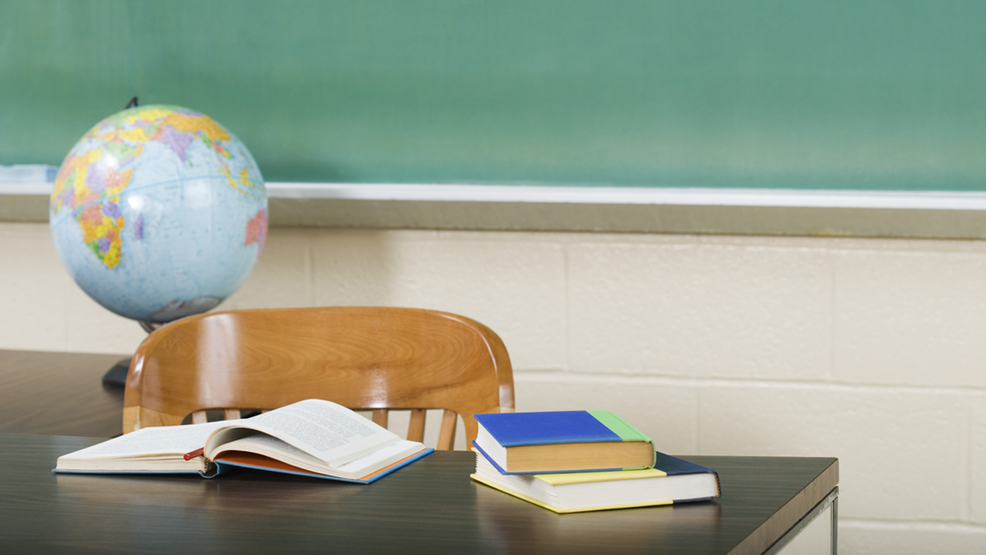 A globe and books sit on top of table in front of chalkboard