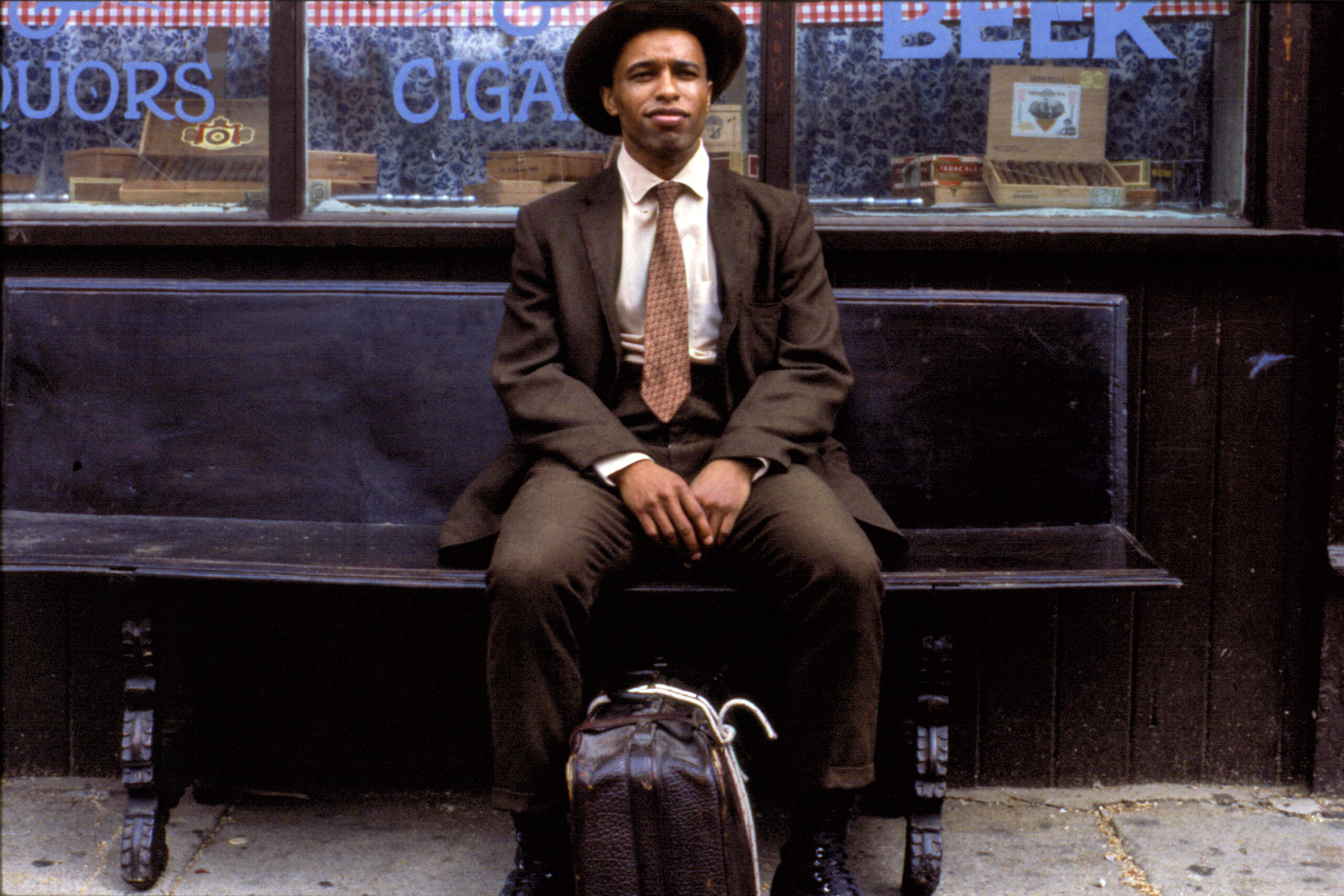 Suited up black man Frank Custer sits on bench