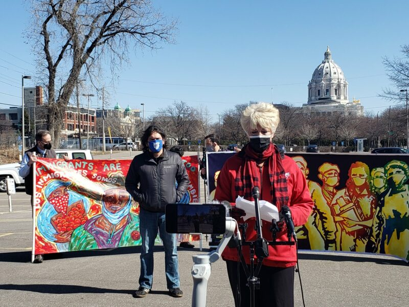 People stand in front of colorful signs, state Capitol Building in background