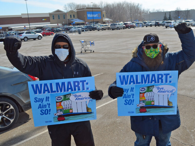 """Men hold up fists and signs that say """"WalMart say it ain't so!"""""""