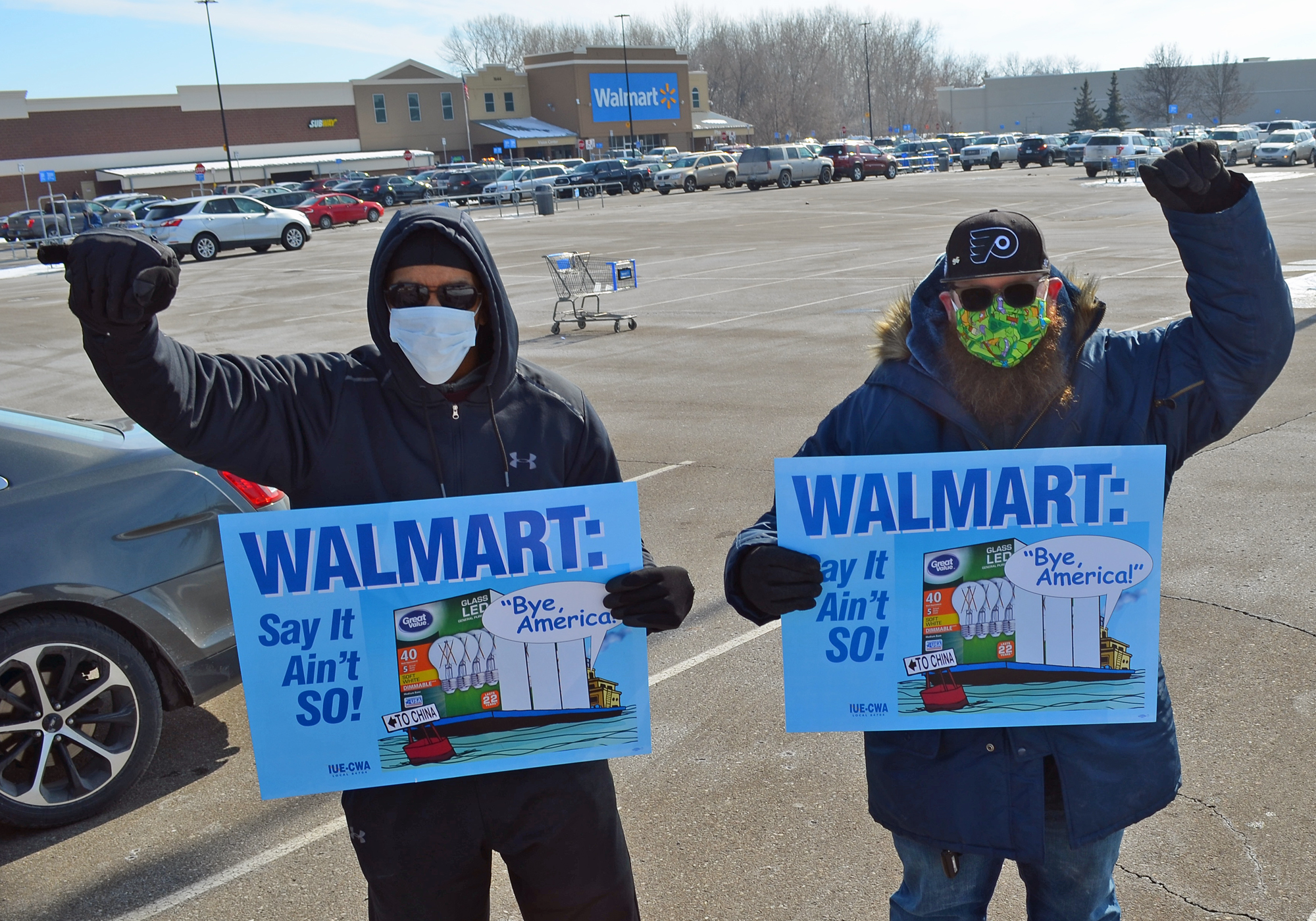 "Men hold up fists and signs that say ""WalMart say it ain't so!"""