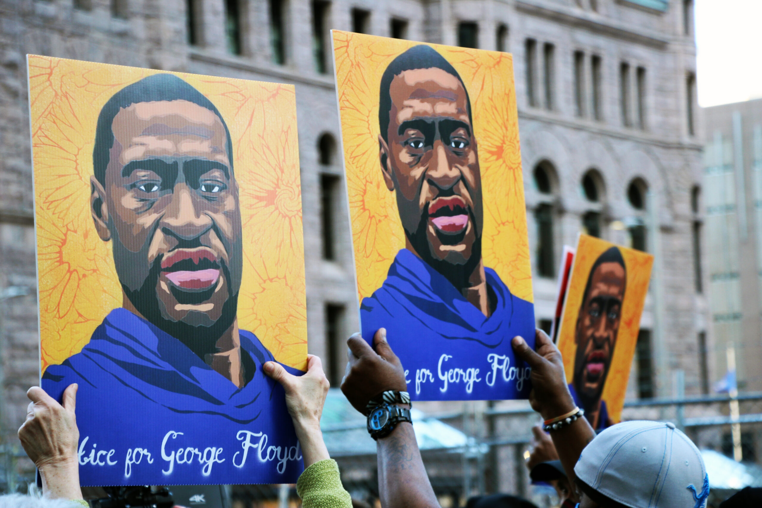 three yellow signs are held up that have George Floyd's face on them