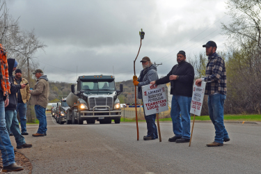 3 men hold signs on the picket line on the street in front of a semi truck