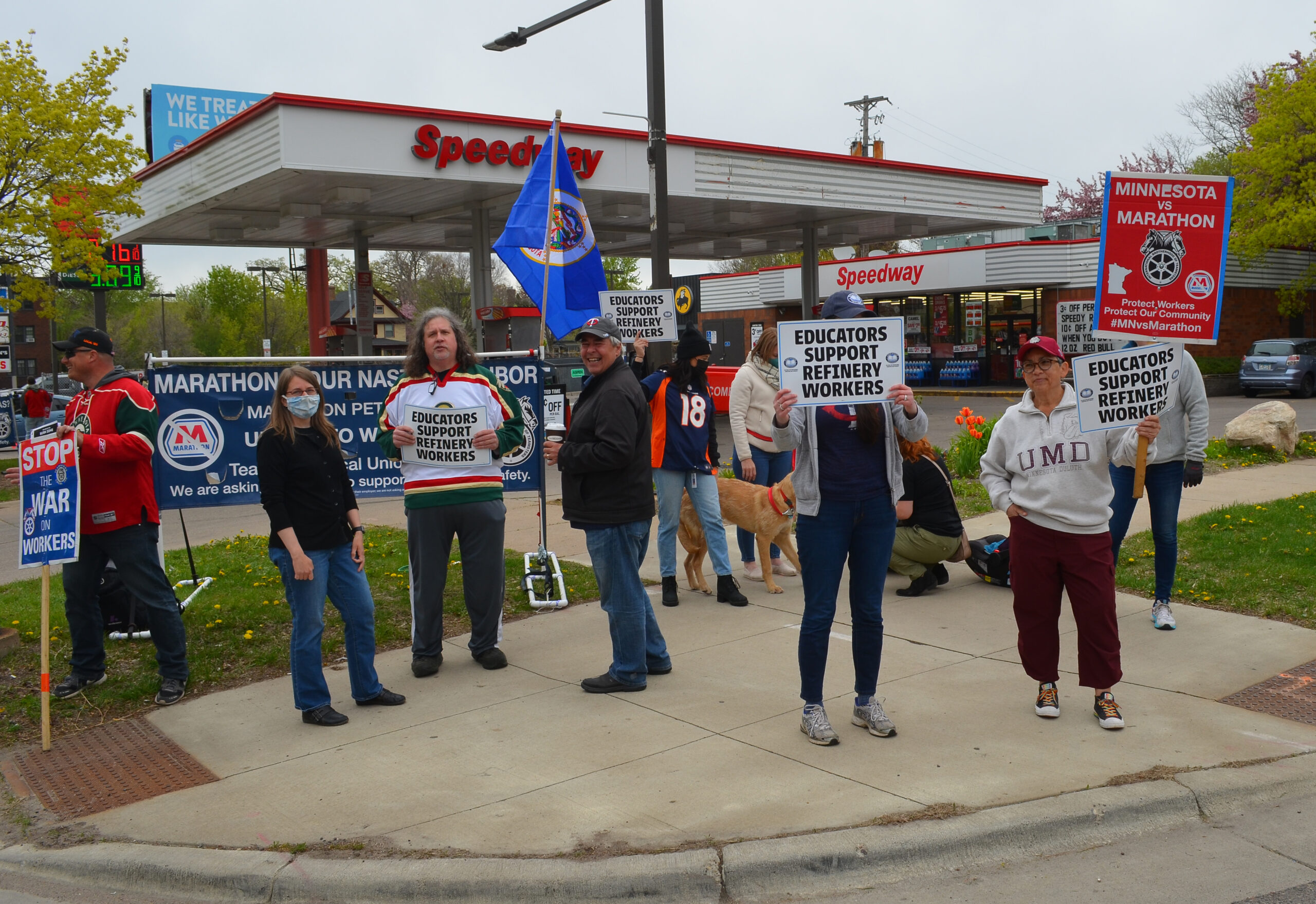"""a group of people stand outside of Speedway gas station with signs reading """"educators support refinery workers"""""""