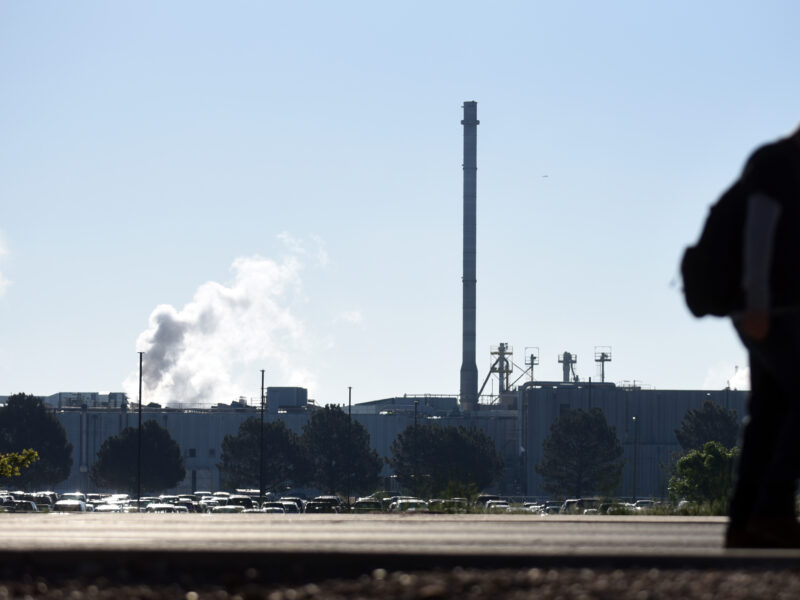 silhouette of a man in front of a blue sky and meatpacking facility towers with smoke pouring out