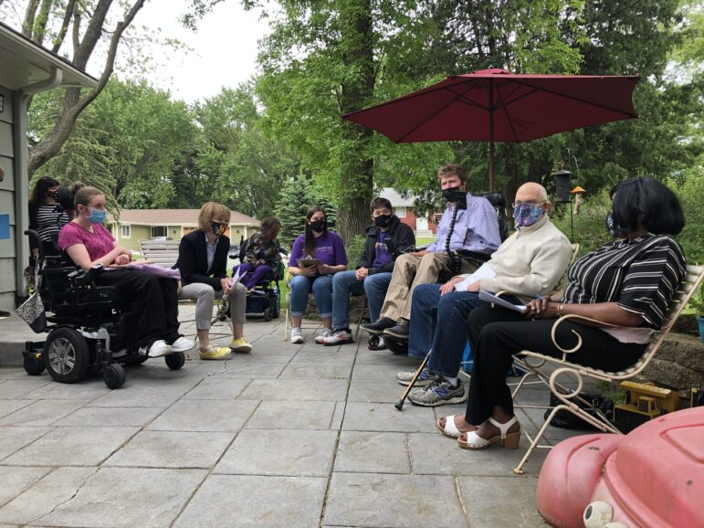 a circle of people wearing masks sitting in chairs outside underneath a red umbrella