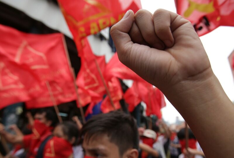 a close up of a fist held up in front of a blurry background of red flags