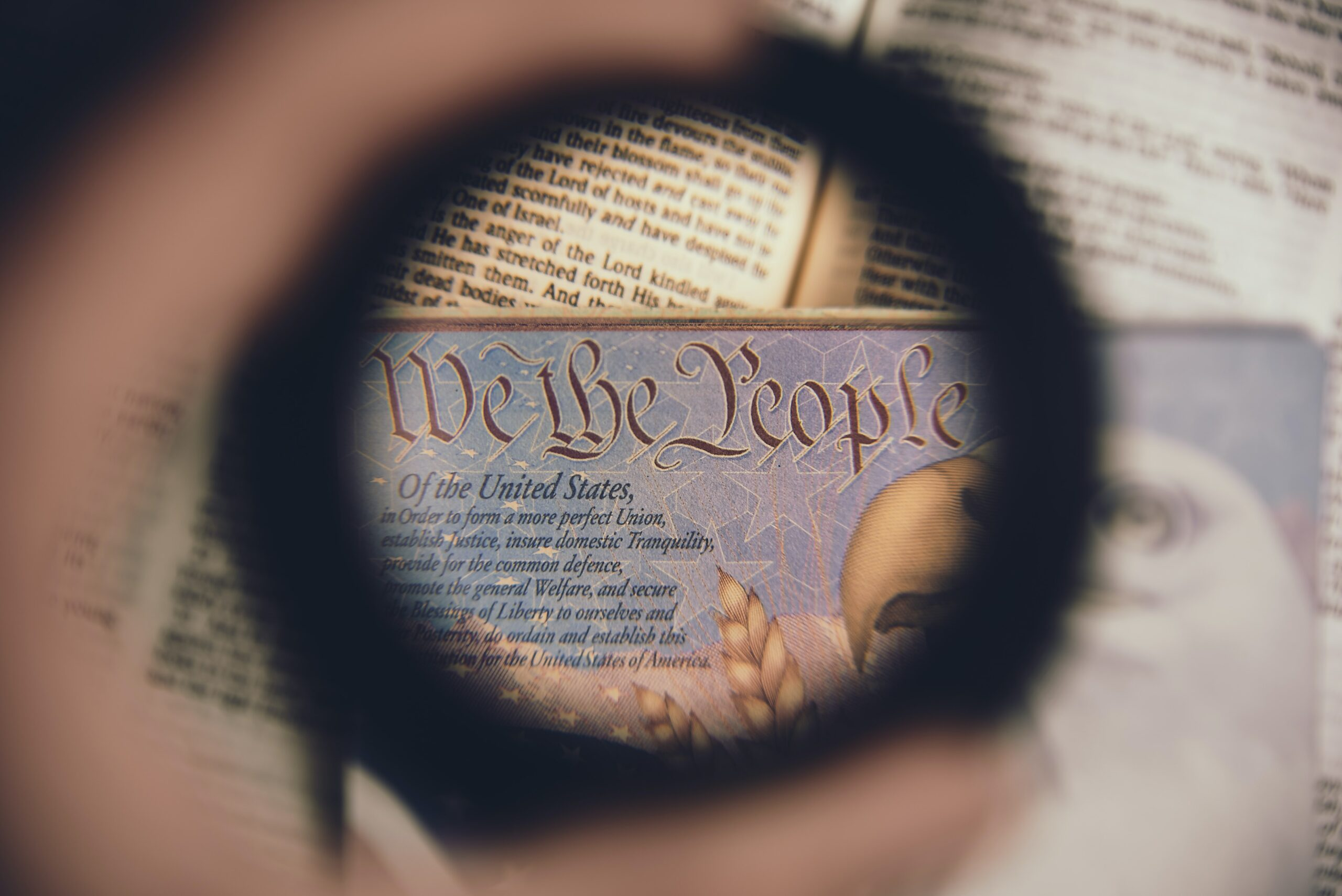 """a blurry hand holds up a lens to the part of the US constitution that reads """"we the people"""""""