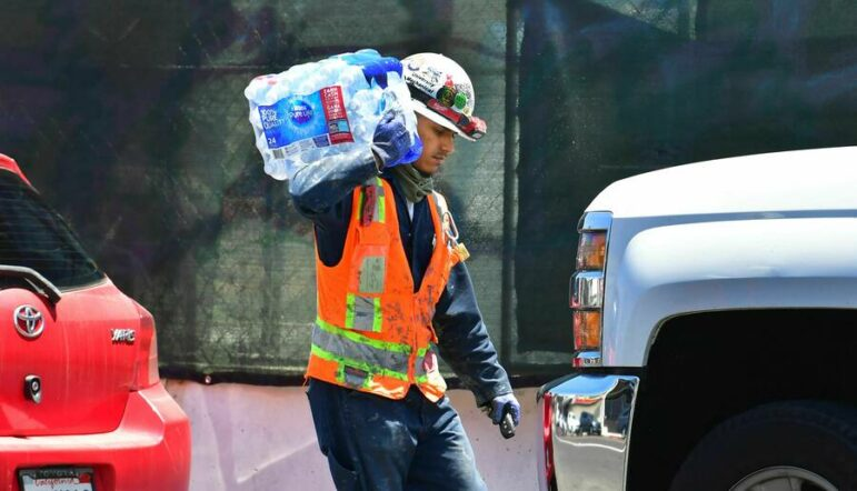 A construction worker in a neon orange vest and white hard hat with stickers carries a bundle of plastic water bottles between two cars