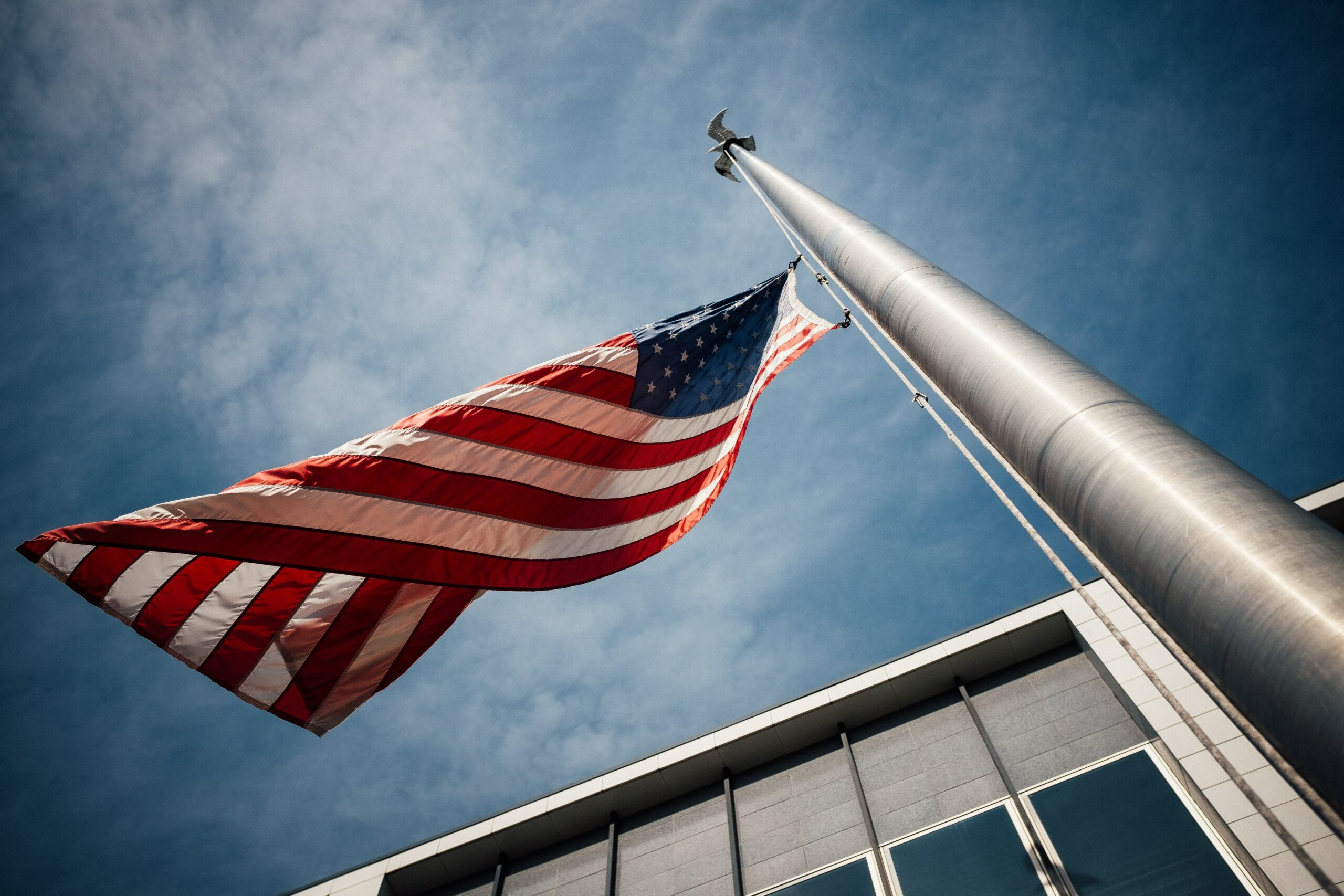 a bottom up view of an american flag attached to a tall silver pole flying in the.wind in front of a grey office building with windows