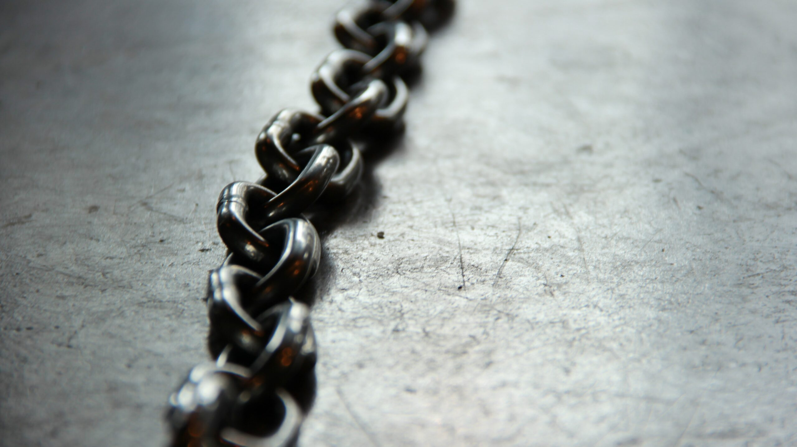 a line of steel chains lie on grey concrete ground