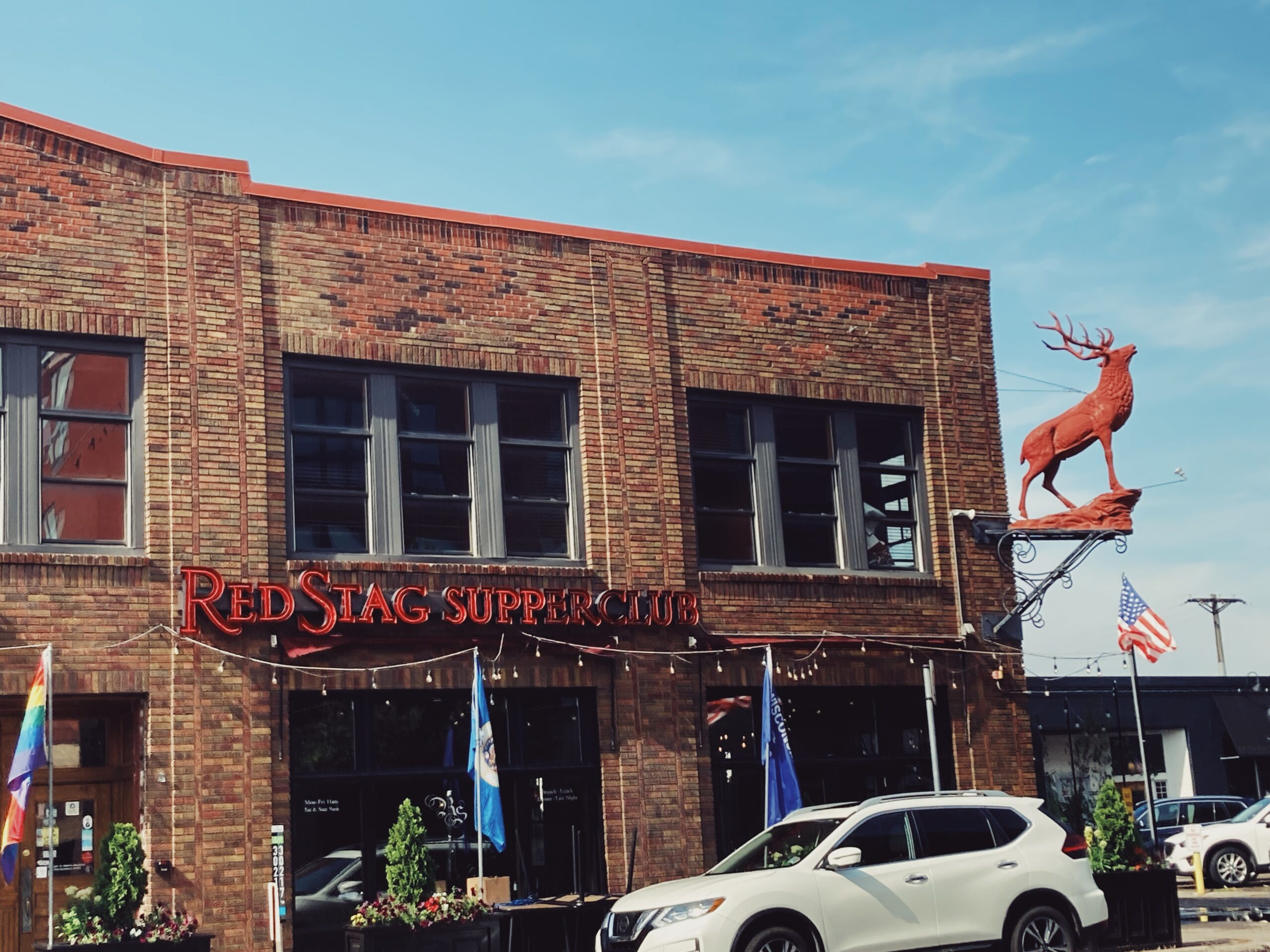 the storefront of the Red Stag Supperclub during the daytime. which has its name in big red letters and a big red stag mannequin hanging off the corner of the brick building