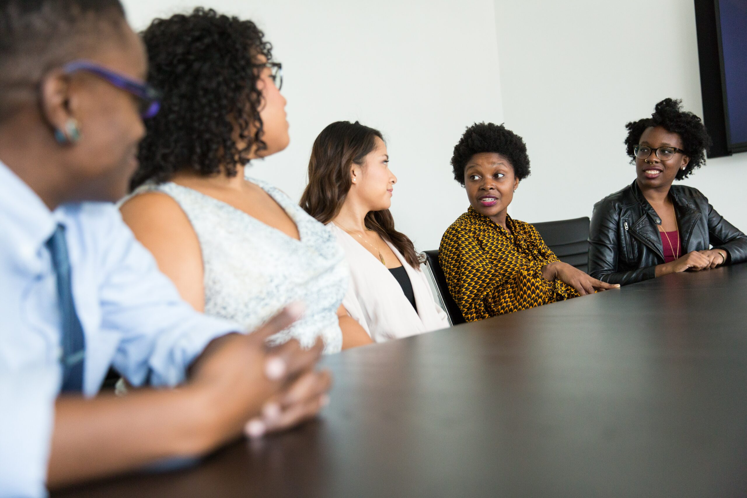 five black women sit at a table facing each other in conversation