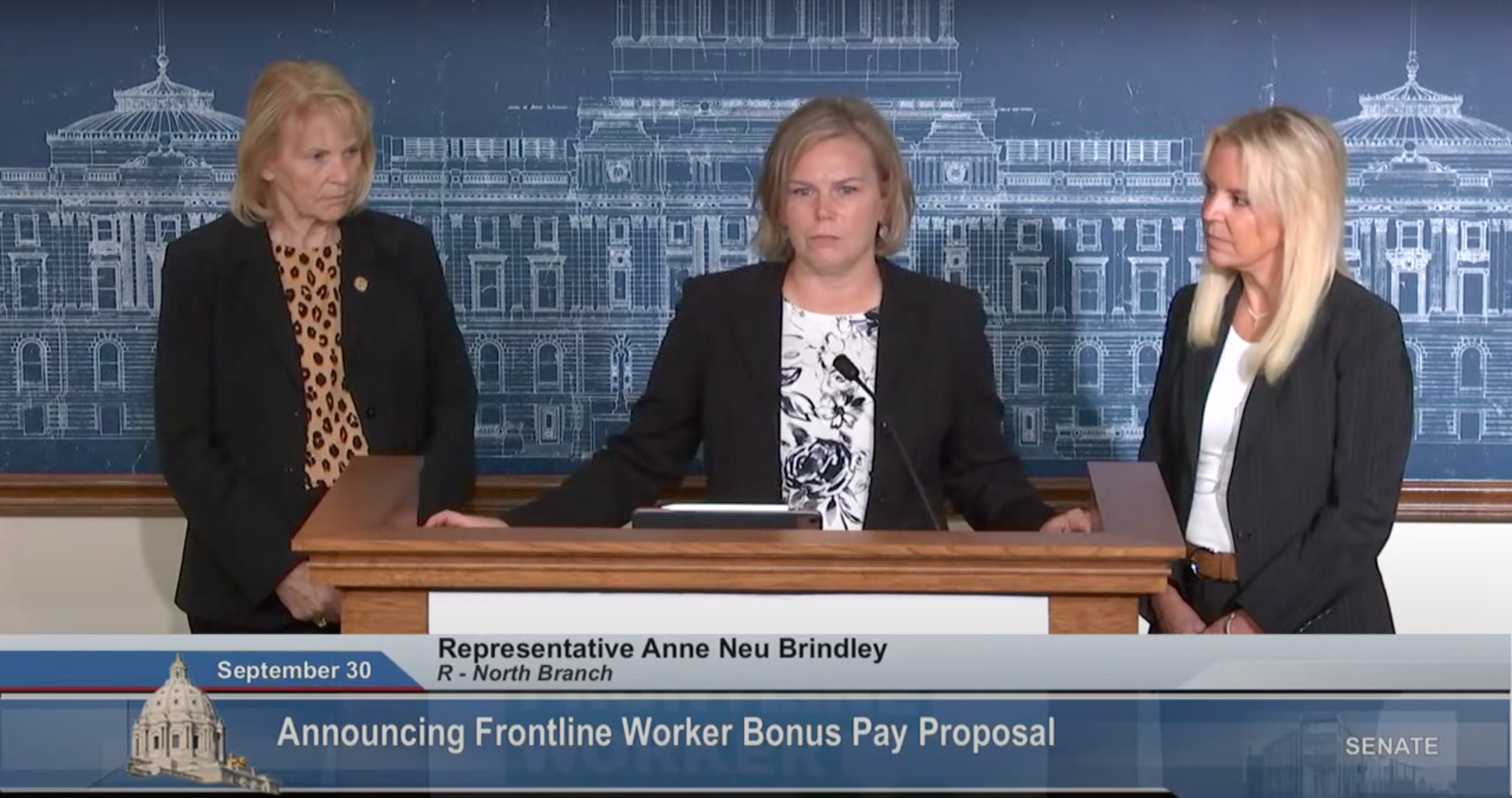 three blonde white women with black blazers stand behind a podium in front of a blue poster of the capitol building