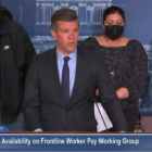 screenshot of press conference man in dark suit and blue shirt standing behind a podium in front of two people one wearing a black sweatshirt and other wearing a black dress and black face mask